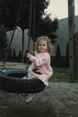 Aviva Finkelstein, age two years, relaxes in a tire swing at the Lubavitch's Children's' Rally