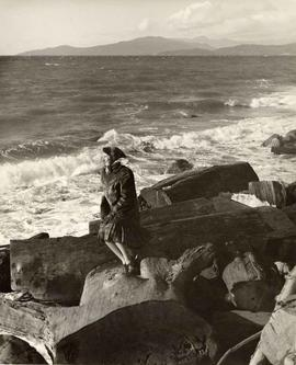 Barbara Landauer standing on log, foot of Harwood St., English Bay