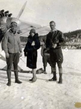 [Two unknown men and an unknown woman posing in front of an airplane in the snow]
