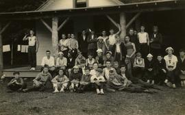 [Large group of unknown boys posing for the camera on the porch of a building]