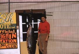 Phyliss Snider standing next to a dead fish which is hanging upside down on a hook