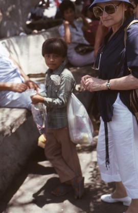 Phyliss Snider and a young boy holding a bag under his arm and a bag in his hands