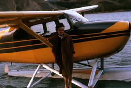 Phyliss Snider in front of an amphibious aircraft in Atlin Lake, B.C