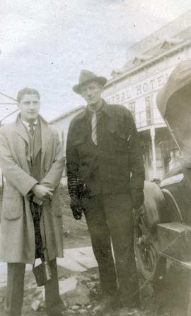 [Dr. Robert Franks and an unknown man standing next to a car]