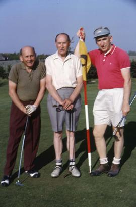 Three unknown men posing for the camera on a golf course