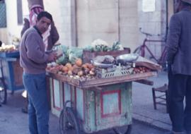 Unidentified man standing in front of a cart loaded with various fruits and vegetables