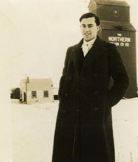 [Unknown man standing in front of a grain elevator]