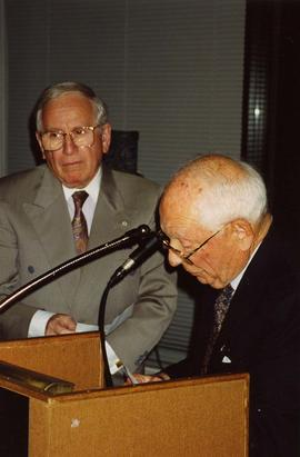 [Joe Segal standing next to Dr. Irving Snider who is looking down at the podium he is standing be...