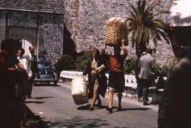 Two women crossing the street carrying woven baskets