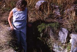 Phyliss Snider standing in a hole in the ground surrounded by rocks and grass