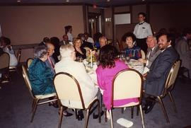 [Dr. Irving and Phyliss Snider sitting with a group of unknown people at a table eating]
