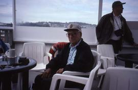 Dr. Irving Snider posing sitting on a chair on a boat