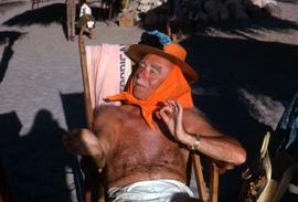 Unknown man sitting in a lounge chair wearing a straw hat with an orange scarf on his head