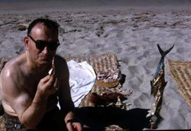 Harry Nemetz sitting on a beach eating a piece of fish with a roasted fish on a stick next to him
