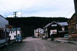 Dirt road in Dawson City with a hotel and store on it