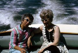 Two unknown women wearing sunglasses sitting on the back of a boat