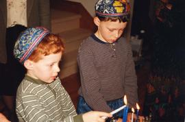 [Jesse and Benjamin Sheftel light the Chanukah candles]