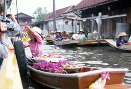 Unknown young woman in a boat handing a string of flowers to tourists on an adjacent boat