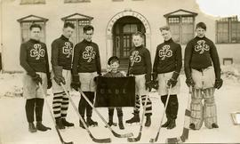 [Hockey team posing for the camera wearing St. Pats sweaters and holding hockey sticks]
