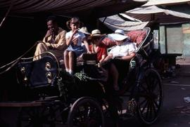 Unidentified man, girl, and two women sitting in a carriage