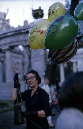 Unknown woman holding several balloons