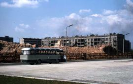 Bus driving by the site of a destroyed building