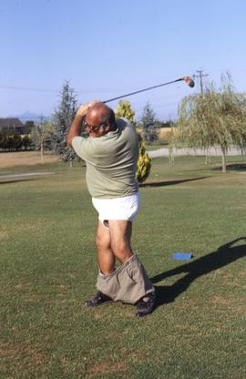 Unknown man mid golf swing with is pants down around his ankles