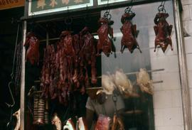 Rows of ducks, chicken and other types of meat displayed in the front window of a butcher shop
