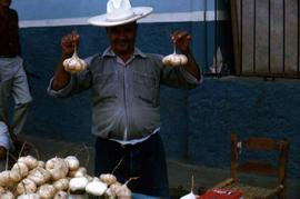 Man holding a root vegetable, likely jicama, in either hand