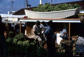 Group of men surrounded by bananas as well as a boat full of bananas on a roof behind them