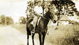 [Unknown woman riding a horse]