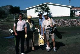 Four unknown men with golf clubs posing for the camera