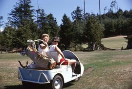 Phyliss Snider and an unknown woman sitting in a golf cart