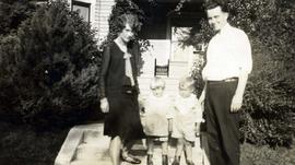 [Unknown man and woman standing on either side of two young children]