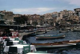 Bay with boats with buildings in the background and tables and chairs in the foreground