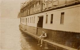 Unidentified man sitting on side of ship