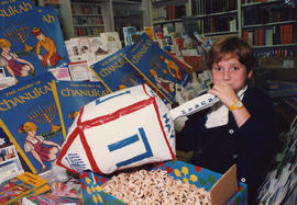 Esther Edel surrounded by Hannukah books and novelties