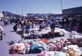 People standing around piles of clothing for sale