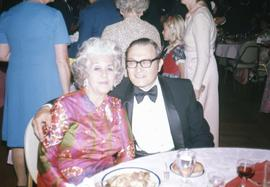 Unknown man and Bessie Karasov sitting at a table and posing for the camera