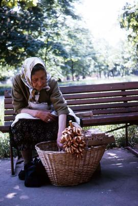 Elderly woman sitting in a park bench selling pastry