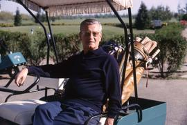 Unknown man sitting in a golf cart with golf clubs on the back of the cart