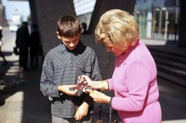 Boy giving Phyliss Snider a choice of Lenin buttons