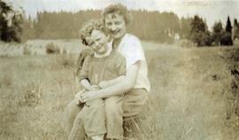 [Unknown woman and a small child crouching in a field of grass]