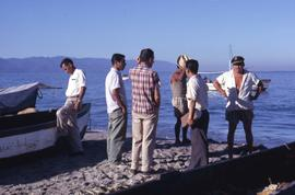 Group of men standing on a beach with one of the men in the right of the image looking at the cam...