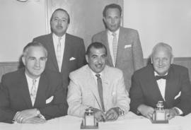 Group of men with two curling trophies