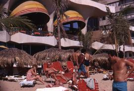 People sitting on chaise lounges under grass umbrellas and other people standing on a beach with ...