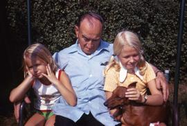 Two young girls and Harry Nemetz sitting on a bench posing for the camera