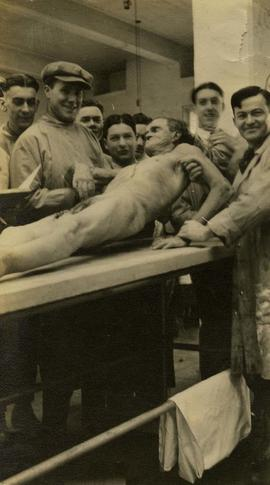 [Group of dentistry students, including Irving Snider in the centre, holding up a cadaver]