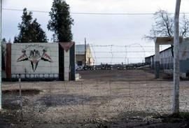 Barbed wire fence in front of a wall painted with the Syrian flag, Syrian coat of arms, and the J...