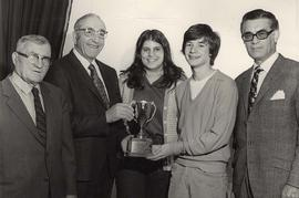 Unidentified boy and girl stand with a trophy, accompanied by three older men